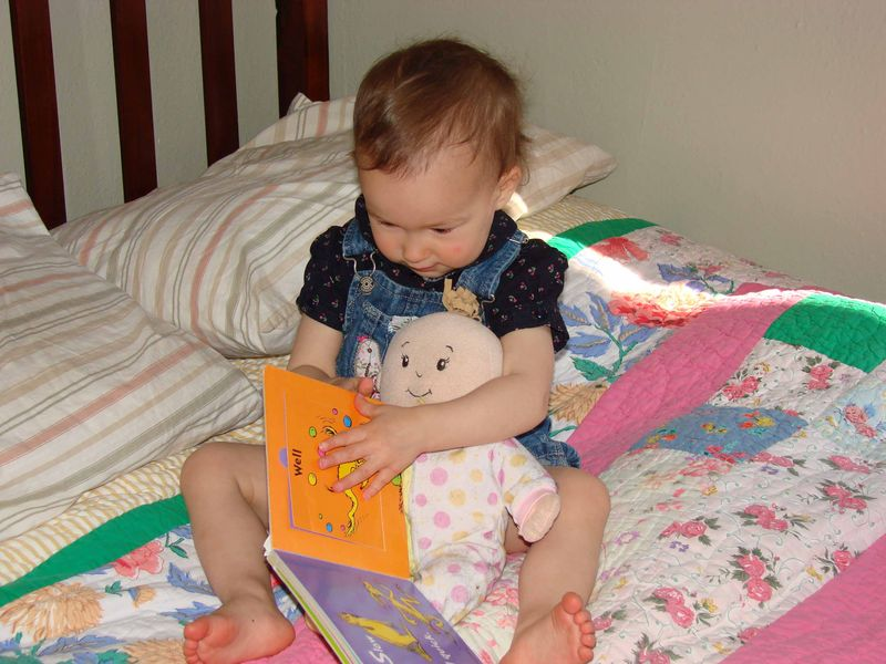 Olive reads to her doll